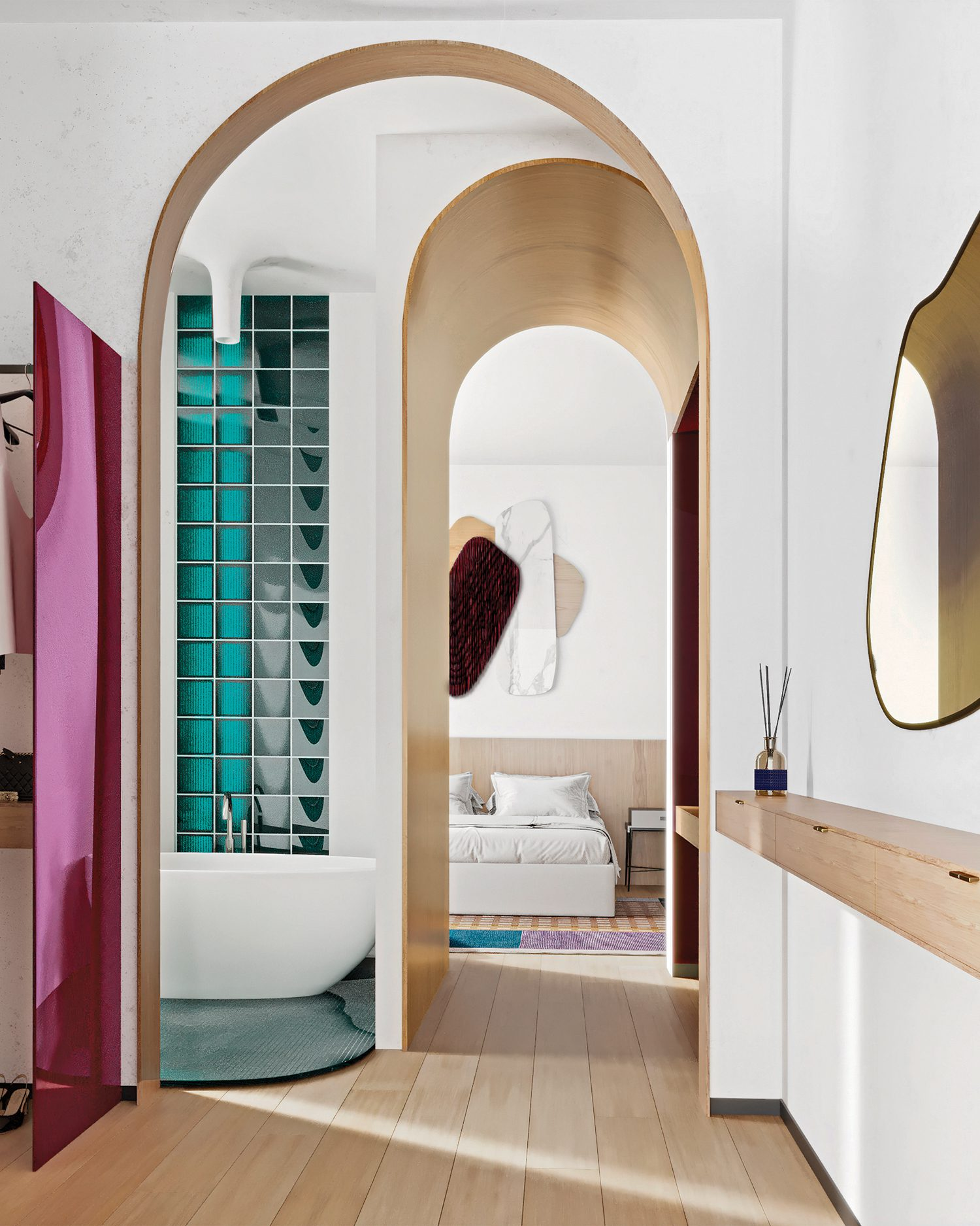 An enfilade of archways connects the bedroom to the bathroom and walk-in closet, where an artsy partition is formed from glass panels sandwiching colored film.