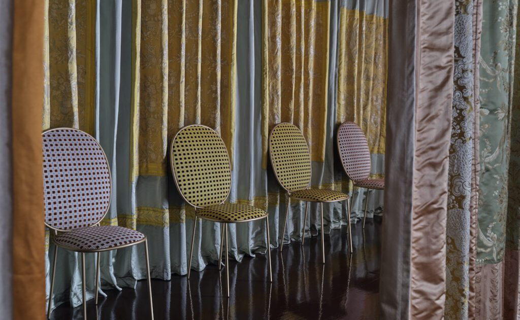 Stay dining chairs in gold and lavender along a curtained wall.