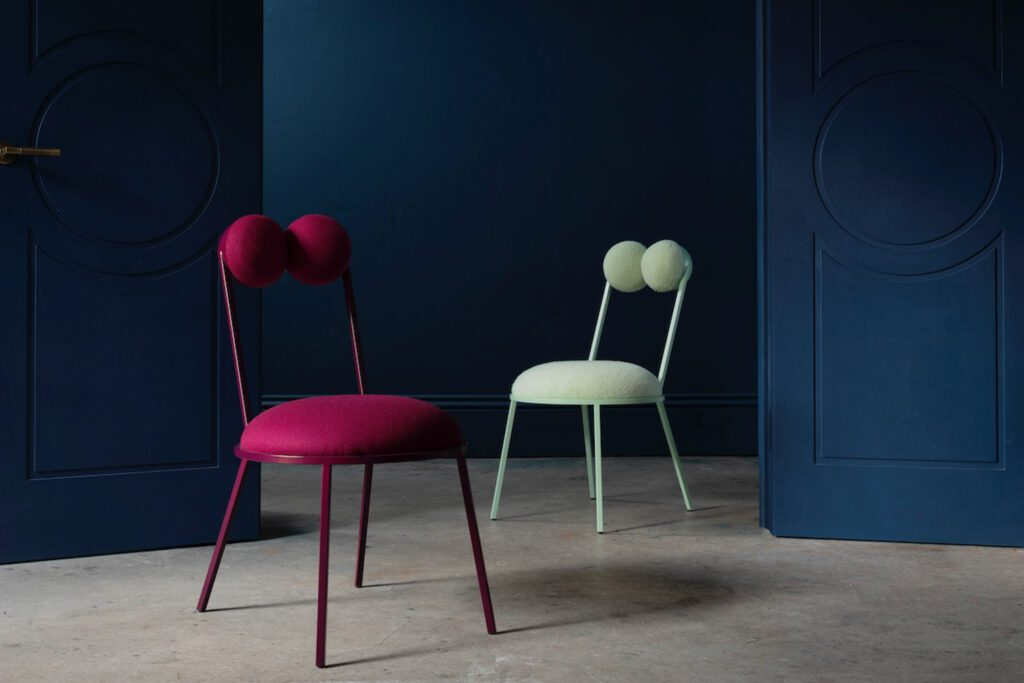 """Described by the designer as """"almost froglike,"""" the powder-coated steel Trevor dining chair has two round upholstered cushions – frog eye-like – forming its back."""