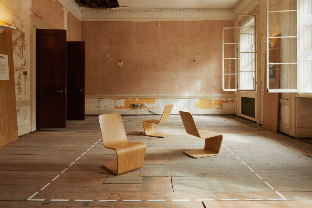 Cantilevered plywood lounge chairs in a room with tiled floor and open windows and no other furnishings.