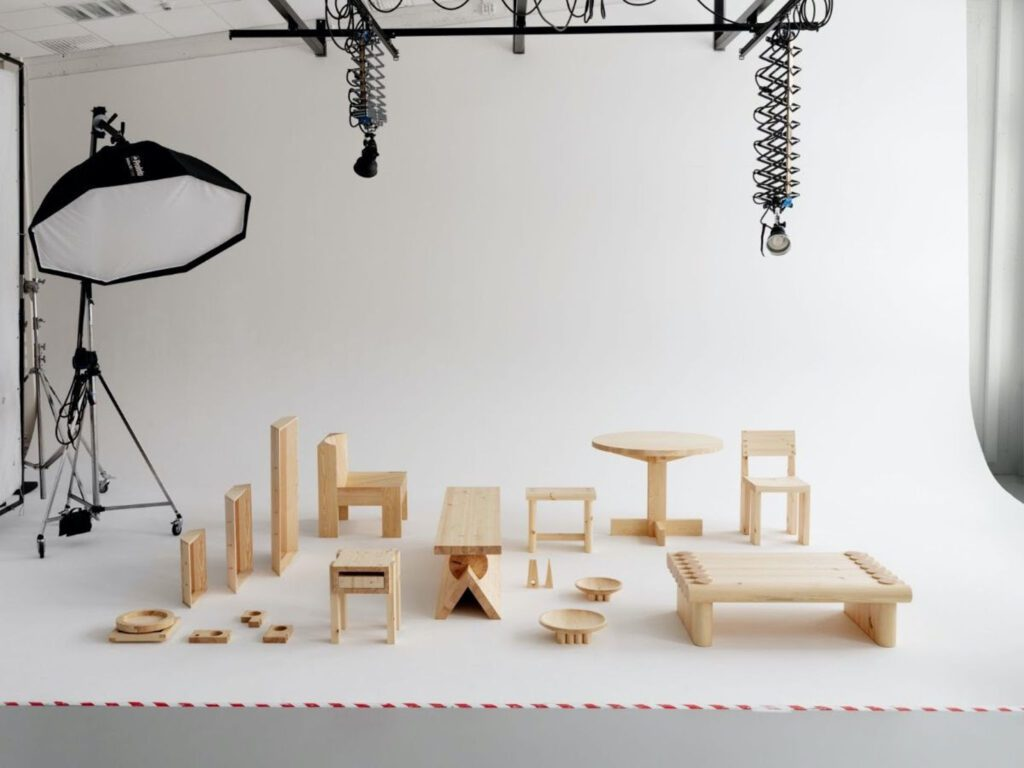 A 12 piece collection of wood furnishings against a photography drop cloth.