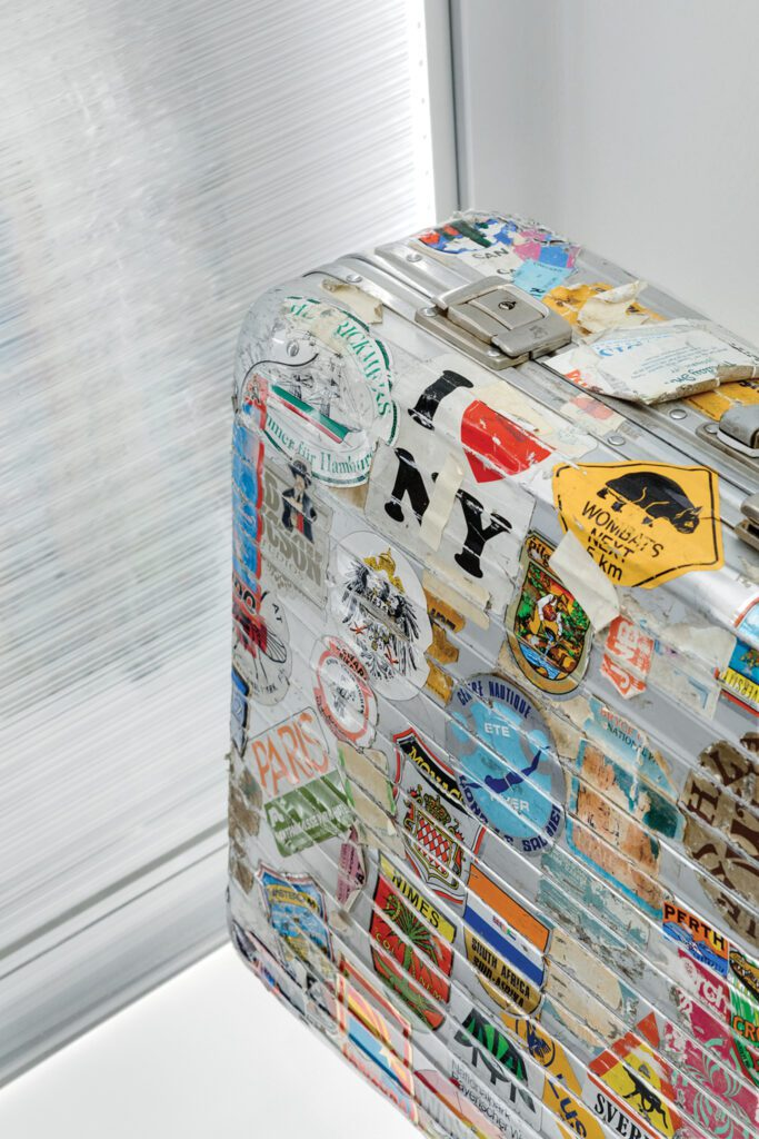 A vintage Rimowa suitcase is emblazoned with travel stickers.