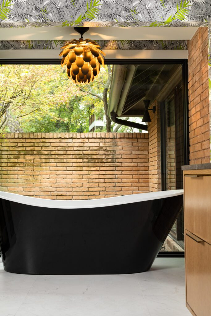 """The main bathroom features a tub enclosed in a glass """"cube"""" that opens to the outdoor shower."""
