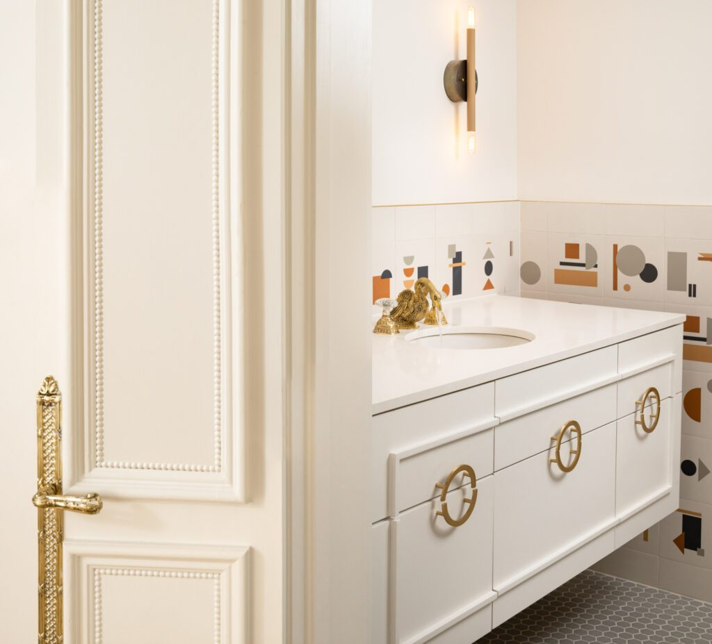 The home's existing fixtures, such as an antique brass swan faucet, are paired with fresh geometric shapes for a playful aesthetic.