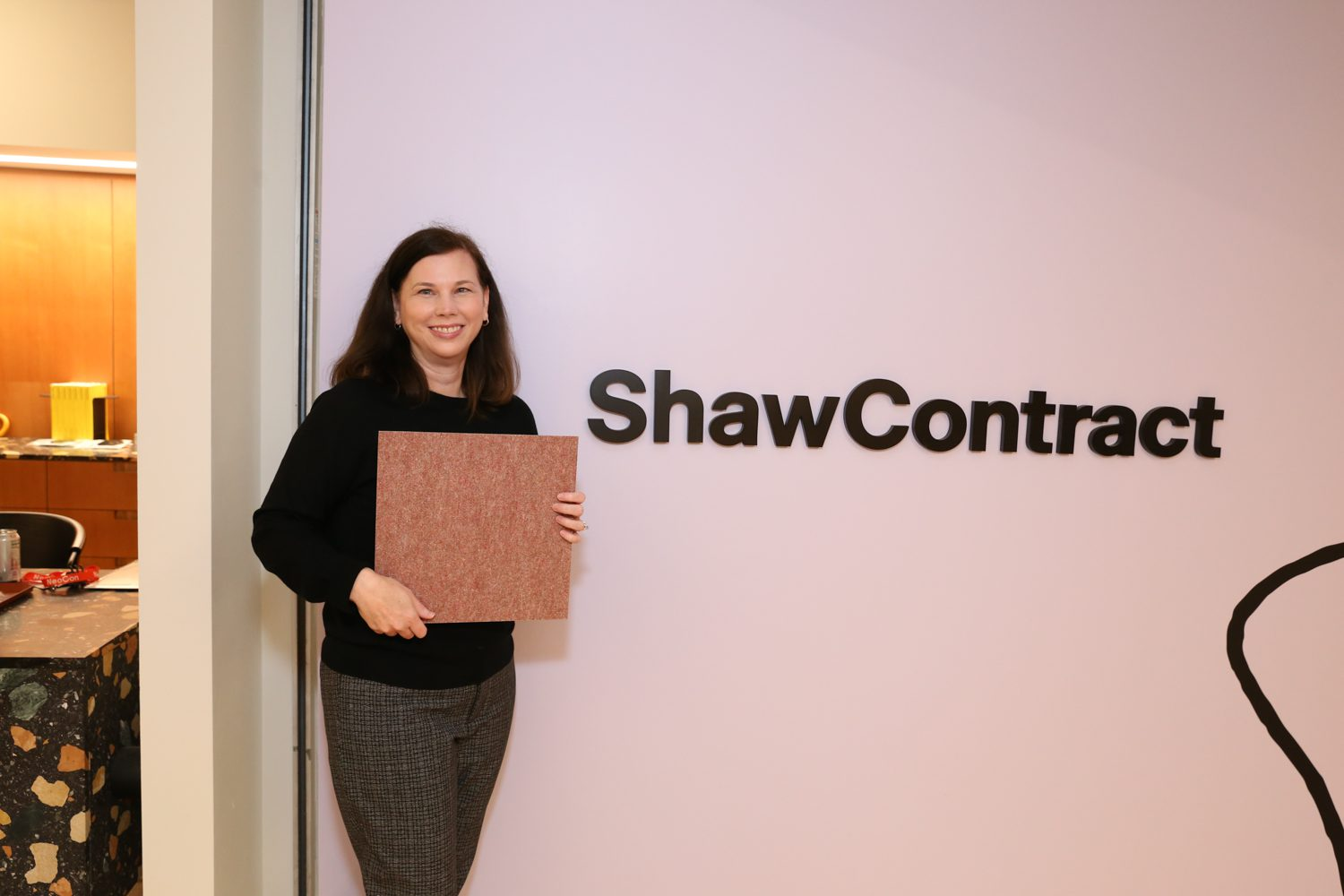 Ashley Ginn, design director community studio at Shaw Contract with the brand's BottleFloor made from 30% PET bottles.