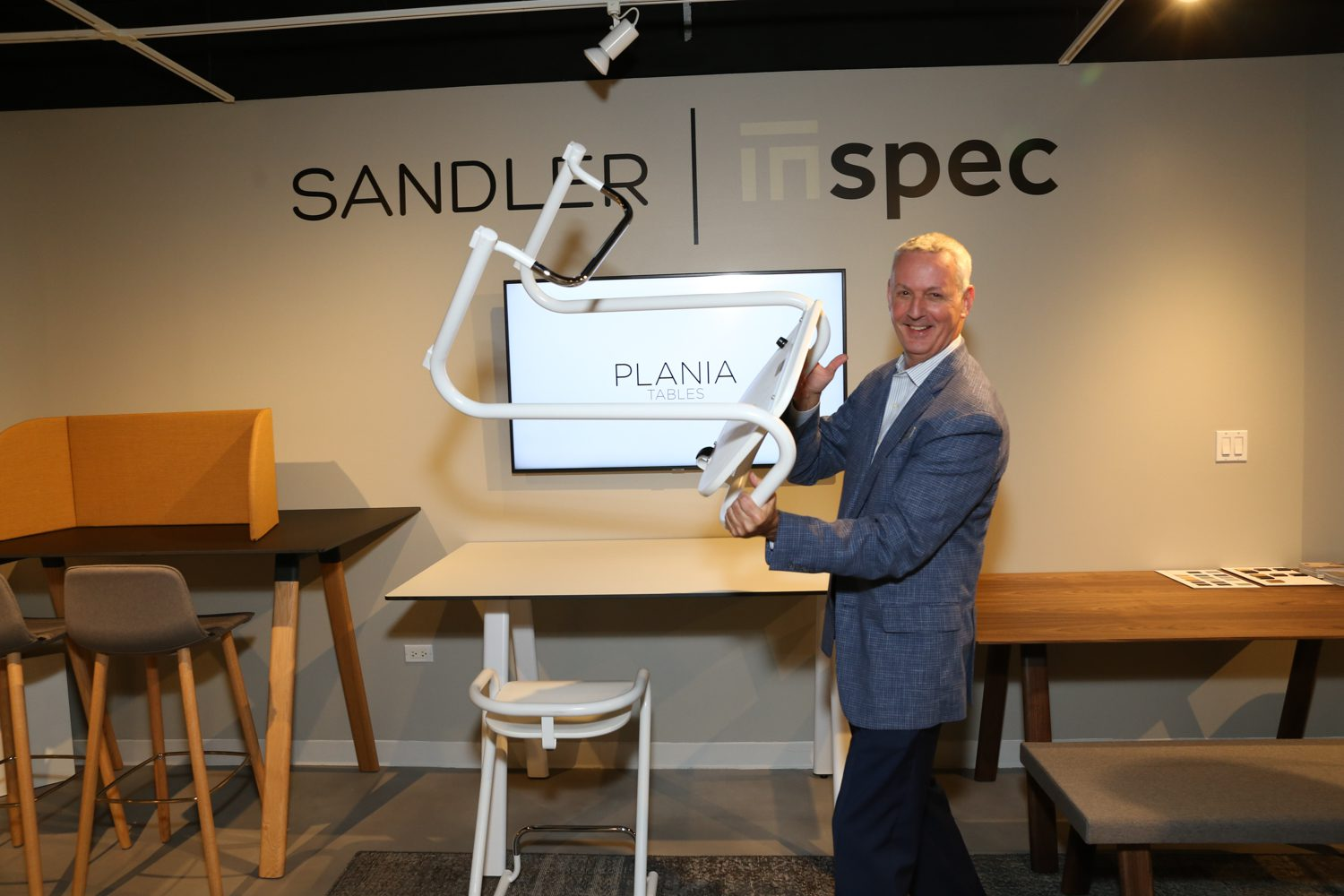 Rusty Wolf, director of sales at Sandler Seating, with the Plania adjustable table.