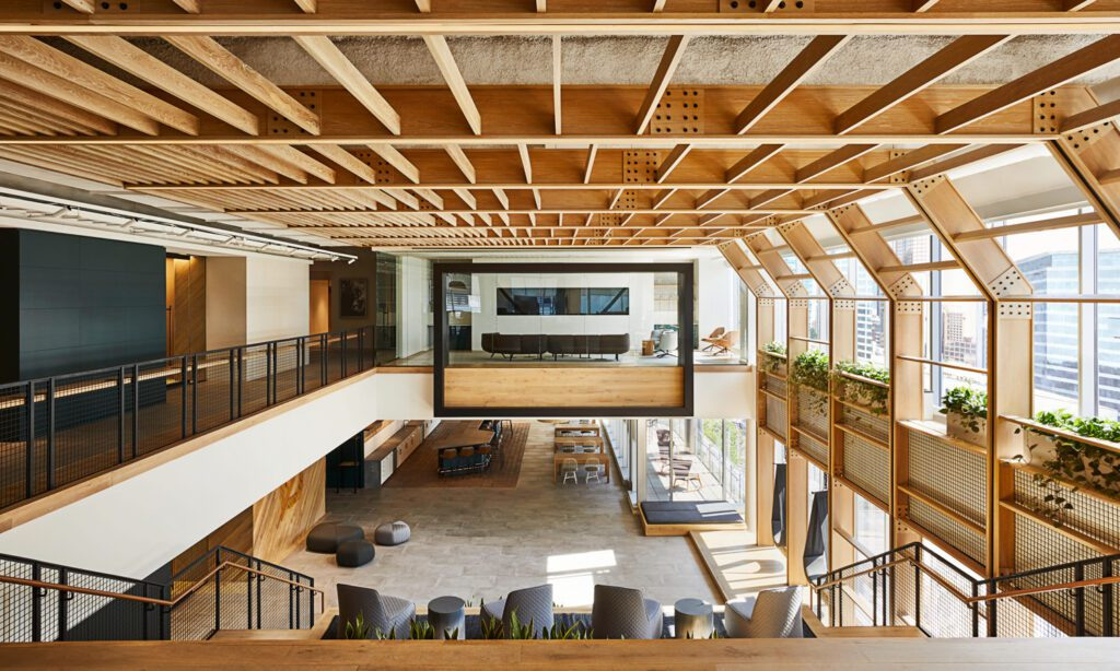 Lending Tree's Town Hall space for all-staff meetings includes a custom wood pergola feature overhead and a connection to the work café below. The custom leather wrapped handrails, cascading plants along the window wall, and rocking chairs on the terrace help to establish the company's culture.