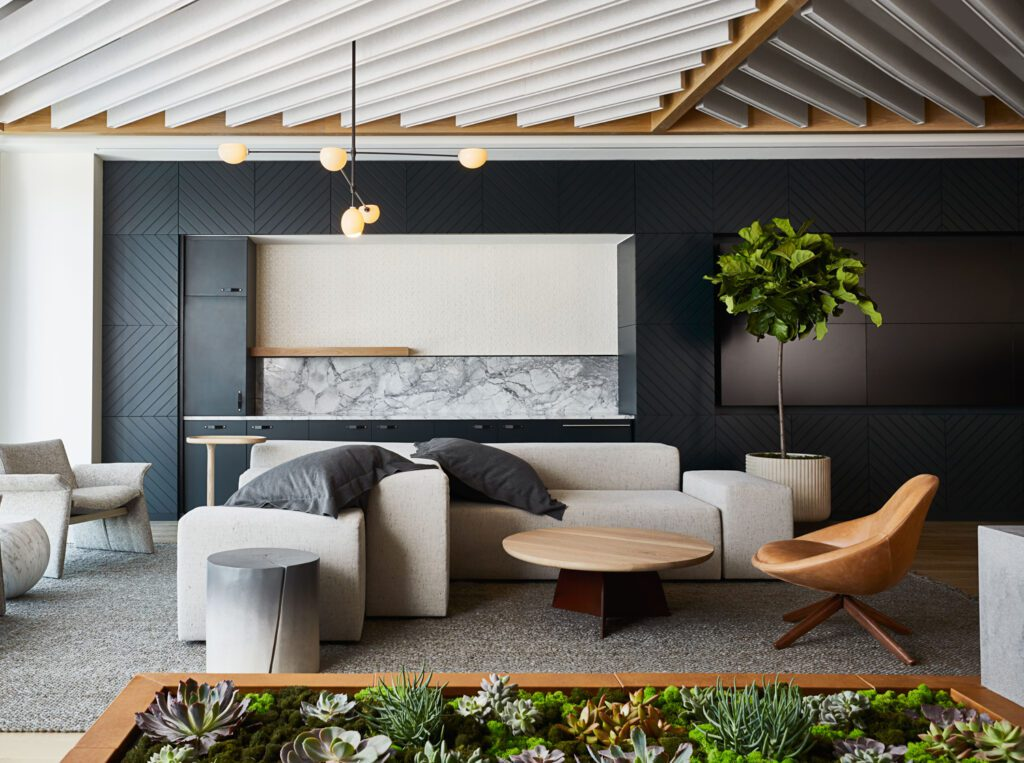 Angles in the felt and wood baffle ceiling feature relate to the leaf structure, and subtly connect back to the company's brand. Other features include a custom metal logo on the lobby desk, interactive media wall, coffee bar, and living room-like furniture.