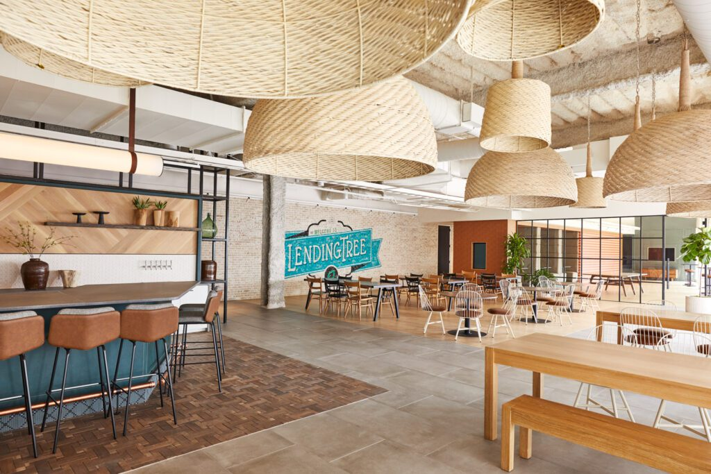 Natural woven light fixtures create a canopy above the café seating. Hardwood flooring, custom designed lighting, furniture, and branded mural on brick wall are all locally sourced. A connection to the game room is seen through an industrial style glass wall.