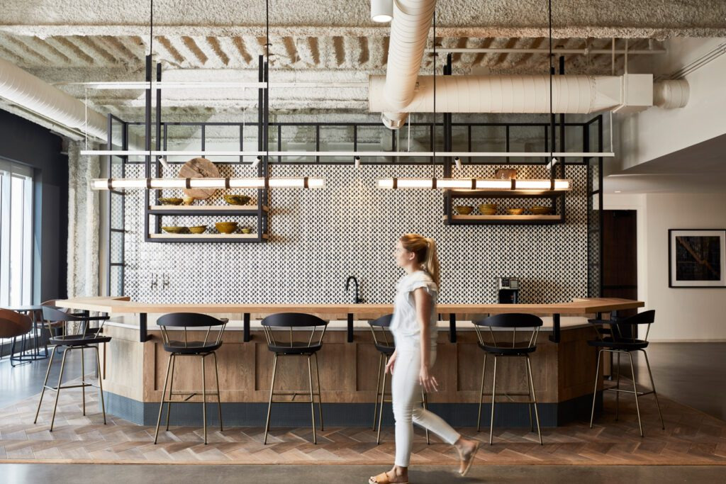 Lending Tree's work cafes are uniquely designed per floor. This featured café includes geometric wood flooring, industrial-style glass elements, and open shelving layered over handmade tile.