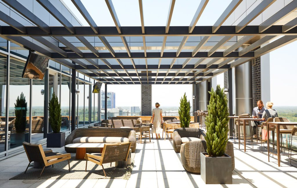 The outdoor terrace features an expansive custom pergola structure overhead with integrated sconce lighting, a mixture of bar and lounge seating, and space defining area rugs.
