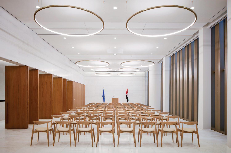 Beneath Rama Mendelsohn pendant fixtures, Hans Wegner's Elbow chairs populate a multipurpose room.