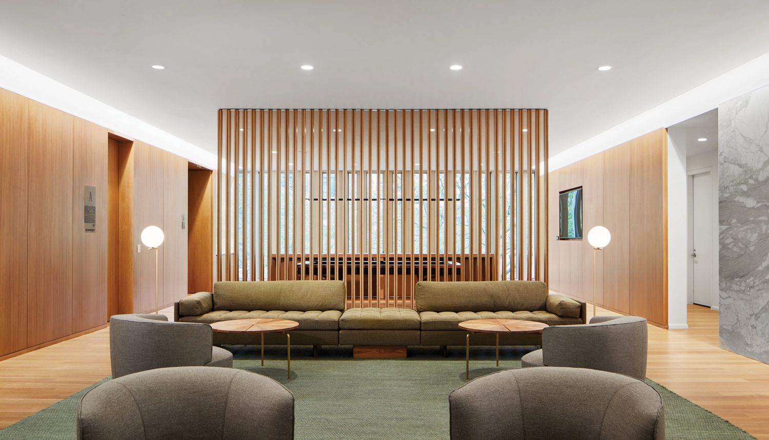 In the delegates' lounge, a custom walnut screen backdrops BassamFellows's sectional sofa and tables and Vincent Van Duysen's Elain armchairs.