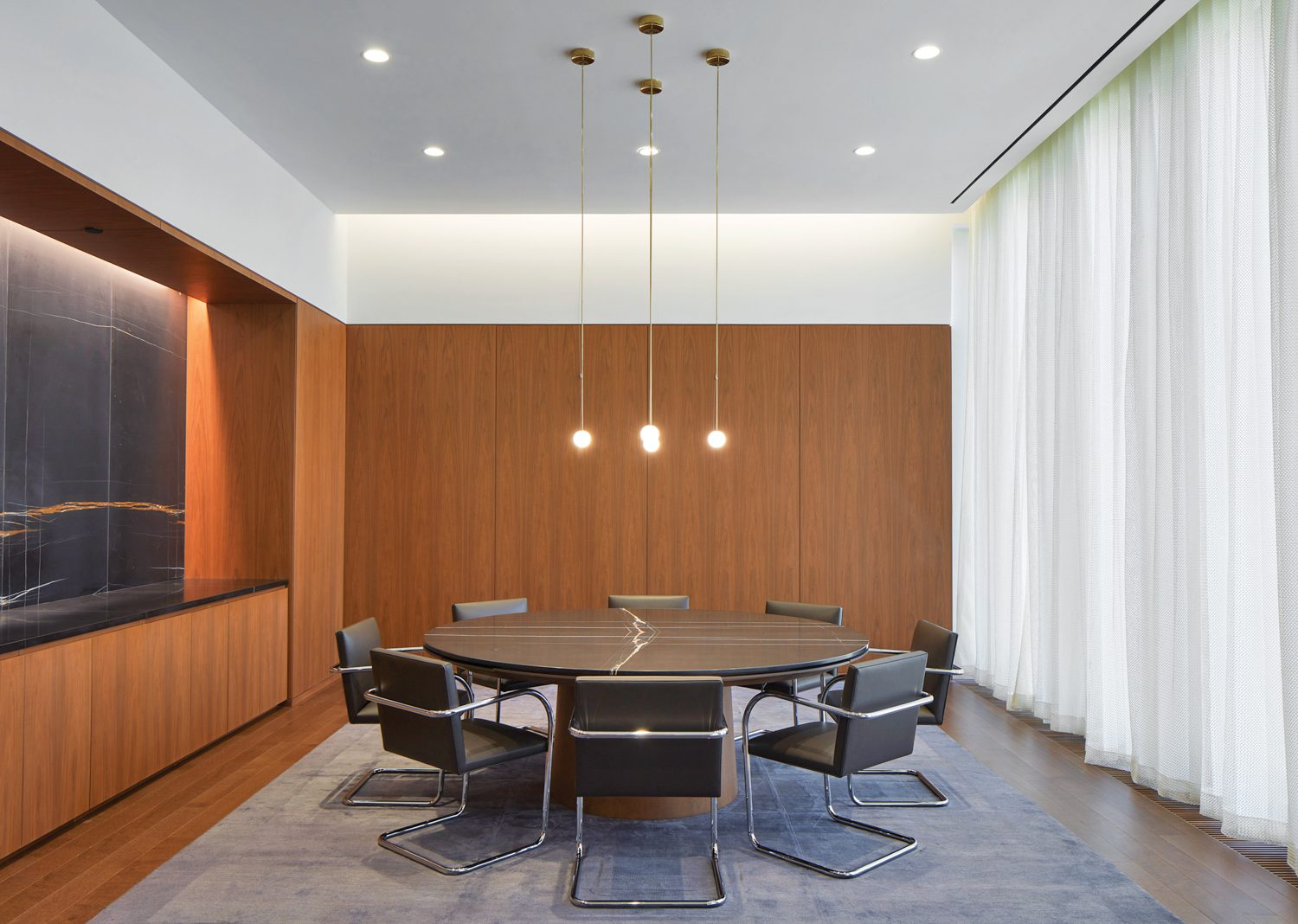 Sahara Noir marble forms the feature wall and custom table's top in an executive meeting room with white oak flooring.
