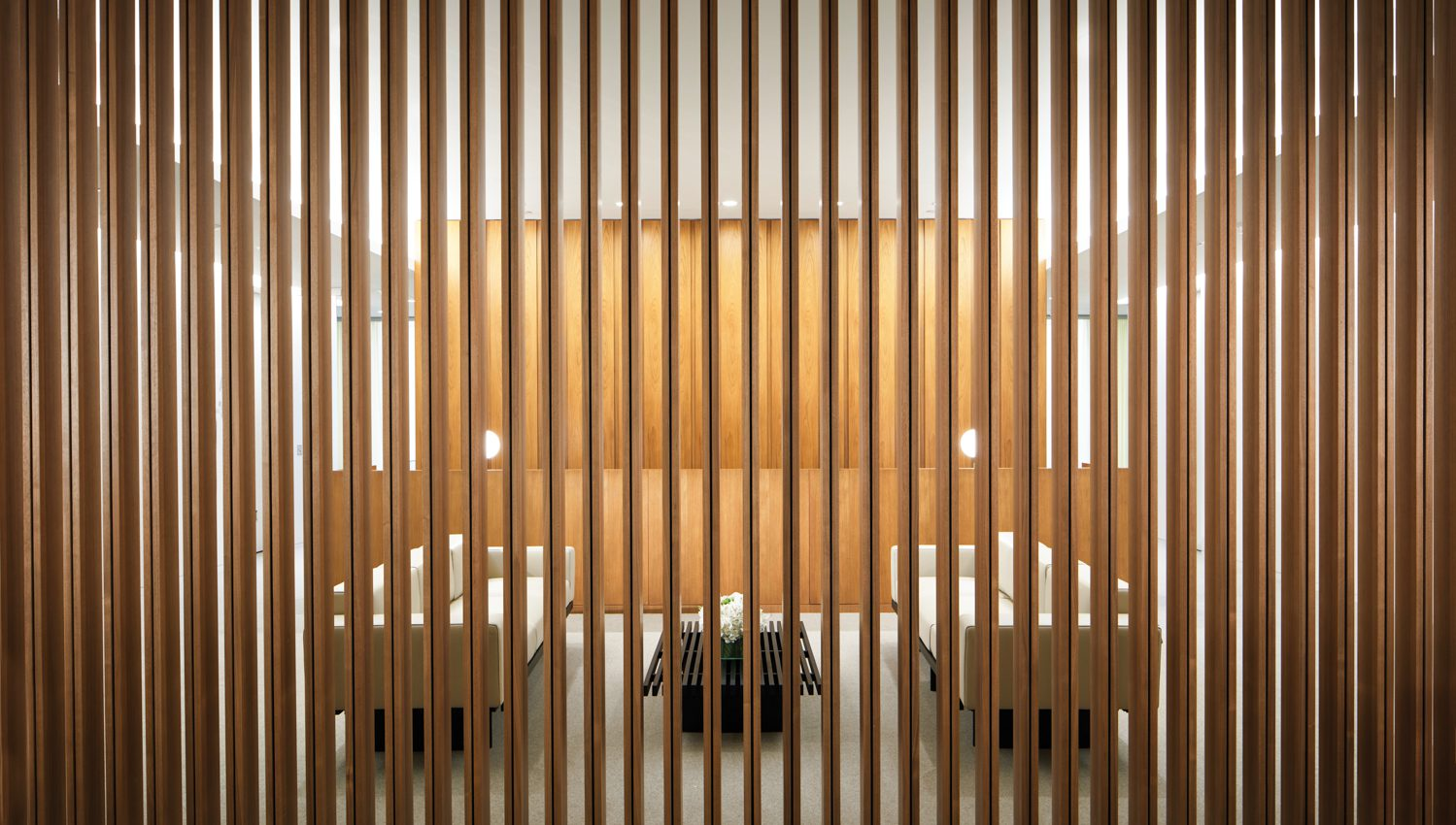 In a screened reception area, leather-covered sofas face a slatted coffee table, all by Charlotte Perriand.
