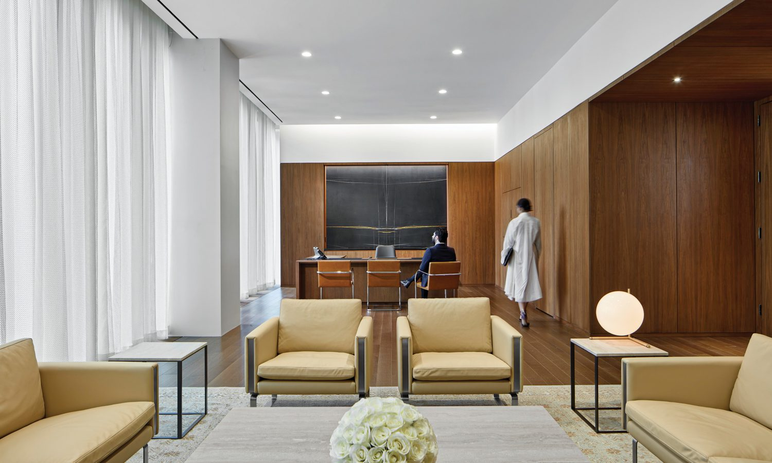Wegner lounge chairs and sofas, Antonio Citterio coffee and side tables, and a custom rug form the seating area in an ambassador's office, where a marble feature wall frames the custom desk and Mies van der Rohe side chairs.