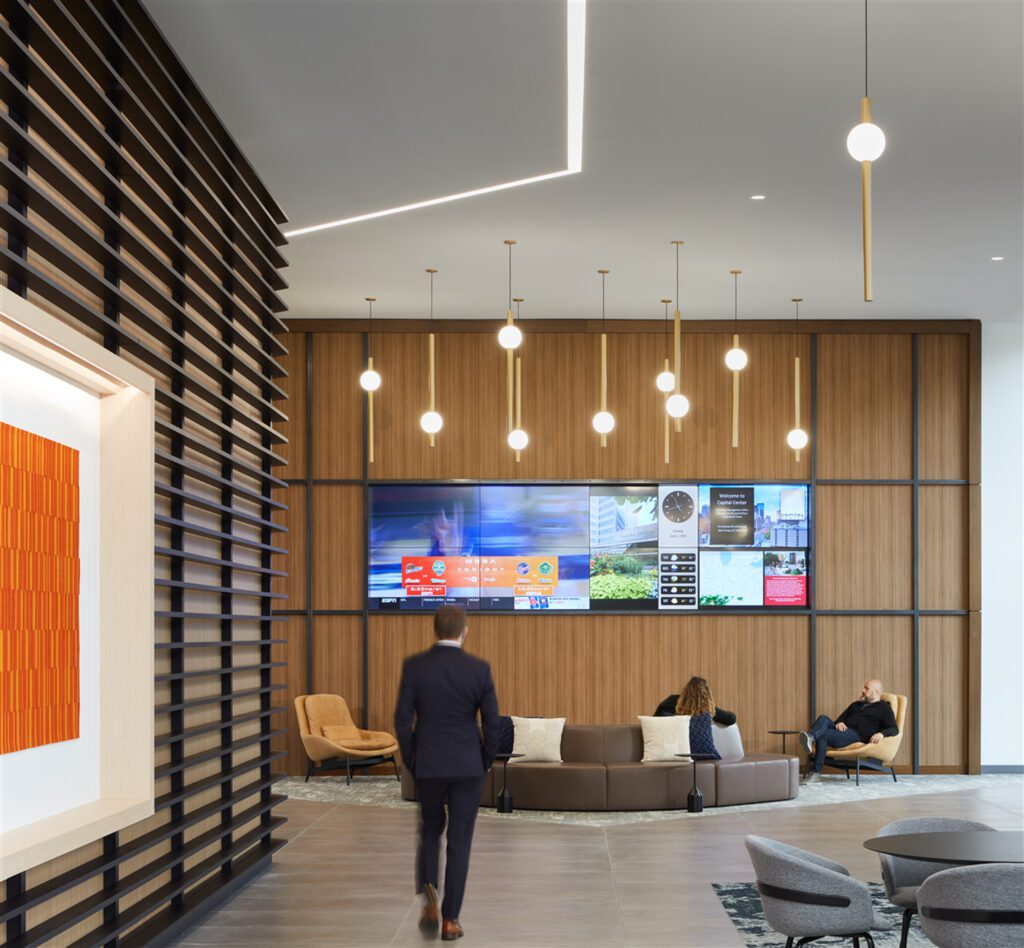 More than a circulation path, a media wall plus furnishings by Blu Dot and National Office Furniture provides a welcoming drop-in space illuminated by recessed Finelite linear lighting.