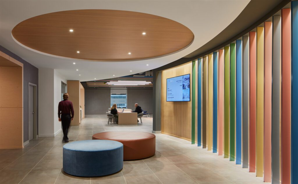 Soft, curved custom millwork in an invigorating array of colors carves the conference center's pre-function space from a tight and complex floor plan.