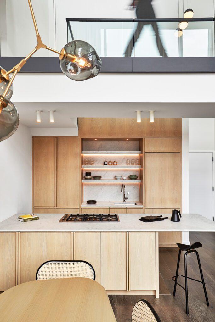Beneath a duplex's glazed catwalk, the custom cabinetry in the kitchen is white oak.