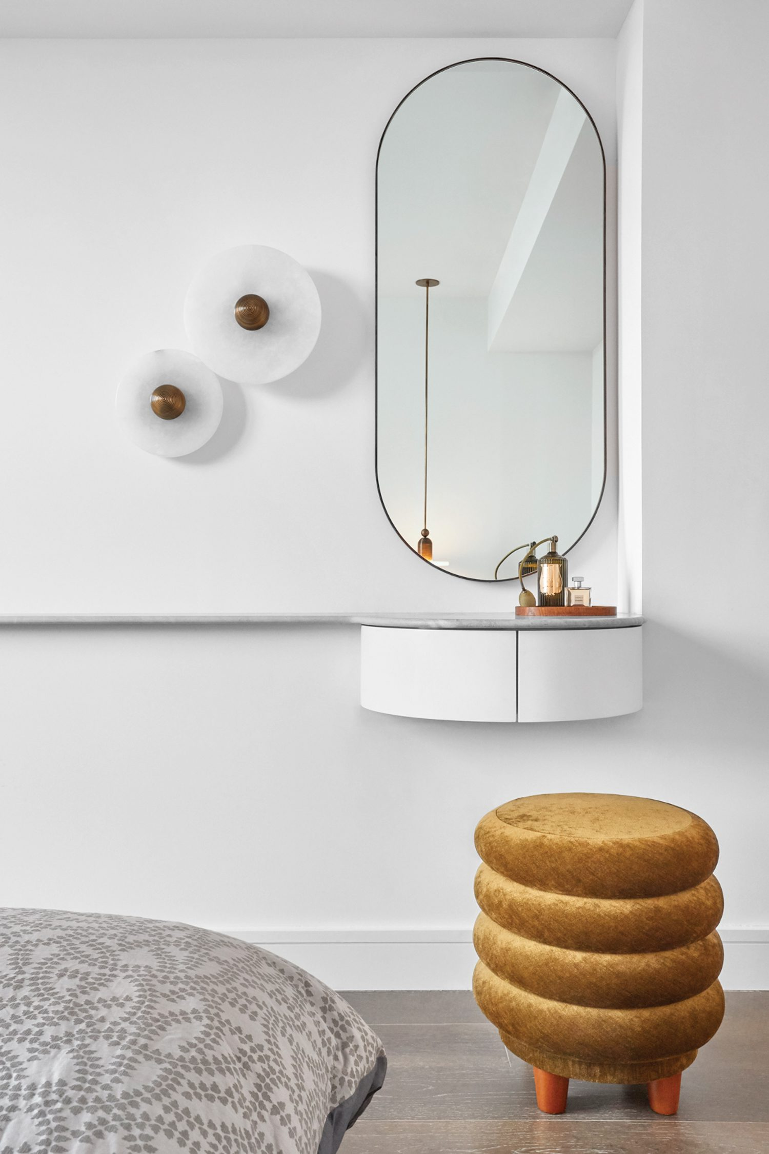 Apparatus Studio's Median sconces and a Capsule mirror by Bower Studios furnish the primary suite's vanity area.