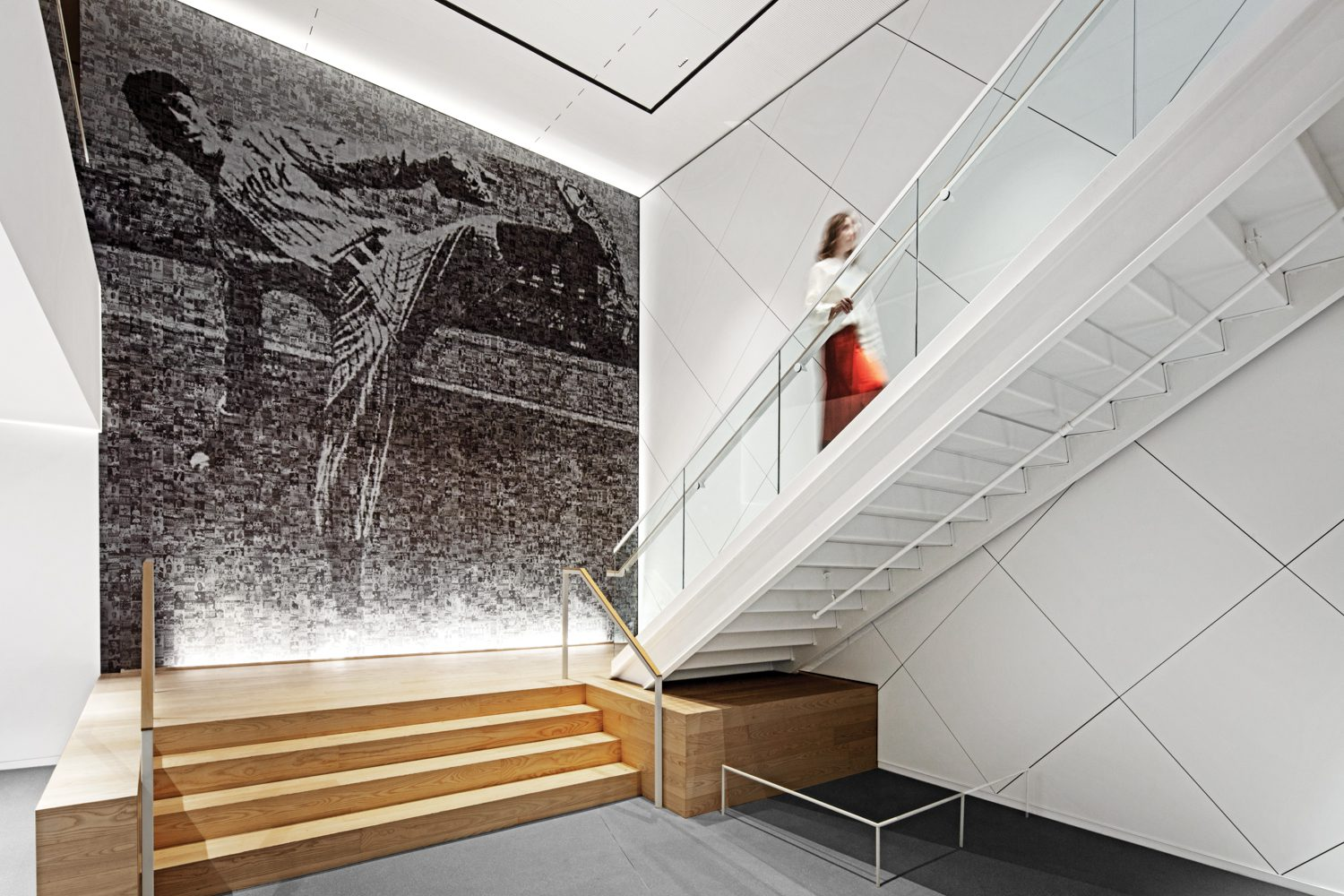 A mosaic of Hall of Fame pitcher Satchel Paige composed of thousands of archival photos of Negro league players anchors a staircase.
